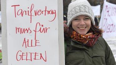 Aktion vor der zweiten Tarifverhandlungsrunde für Film- und Fernsehschaffende in München. Frau mit Plakat: Tarifvertrag muss für alle gelten