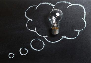 Eine Glühbirne in einer mit weißer Kreide auf einer schwarzen Tafel gemalten Sprechblase
