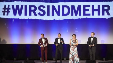 Die drei Moderatoren und die Moderatorin des Deutschen Schauspielpreises stehen auf der Bühne vor einem großen auf die Leinwand projizierten Transparent mit der Aufschrift #wirsindmehr