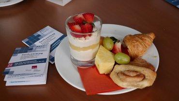 Croissant mit Obst auf Teller und Tarifvertrag für die Hosentasche