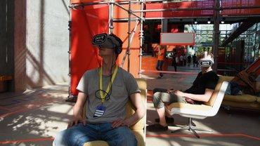 Zwei junge Männer sitzen auf Stühlen und tragen VR-Brillen, mit denen sie einen 360°-Film schauen