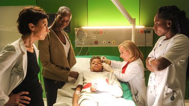 """""""Dr. Klein - Pläne"""": Sammy Kahindi (Simon Johnson) liegt in einem Untersuchungsraum auf der Liege. Um ihn herum stehen Prof. Dr. Nevin Gül (Renan Demirkan), Grace Kahindi-Bäumer (Florence Kasumba), Dr. Valerie Klein (ChrisTine Urspruch) und Martha Obongo (Charity Laufer). Dr. Klein trägt Latex-Handschuhe und verarztet Sammys Platzwunde an der Schläfe."""