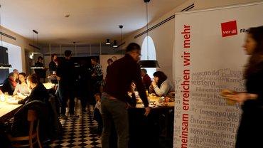 """An mehreren Tischen sitzen Menschen und essen, rechts im Bild ein Banner der ver.di-FilmUnion mit dem Text """"Gemeinsam erreichen wir mehr"""""""