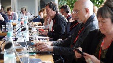 Menschen sitzen an Tischen mit Mikrofonen, tragen Kopfhörer und arbeiten zum Teil an ihren Laptops