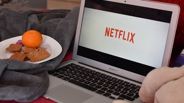 Netflix-Schriftzug auf einem silbernen Laptop. Daneben eine Kuscheldecke und eine Orange