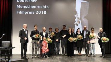 Preisträger des Deutschen Menschenrechts-Filmpreises 2018 stehen auf einer Bühne, zum Teil mit Blumen in der Hand