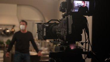 """Schauspieler Herbert Ulrich trägt im Hintergrund bei den Proben für die Telenovela """"Rote Rosen"""" eine Mund-Nasen-Bedeckung. Im Vordergrund eine Kamera, die ihn aufnimmt."""