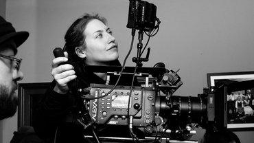 Die Kamerafrau Doro Götz seitlich im Profil. Sie schaut in die rechte Bildecke, unter ihrem Kopf ist die Filmkamera, die sie mit dem rechten Arm steuert. Das Bild ist schwarzweiß.