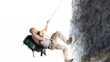 Ein Mann mit schwerem Rucksack zieht sich an einem Seil einen steilen Berg hinauf