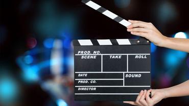 Eine Filmklappe wird von Händen geöffnet, dahinter verschwommener Hintergrund
